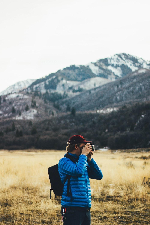 man standing near mountain taking photo
