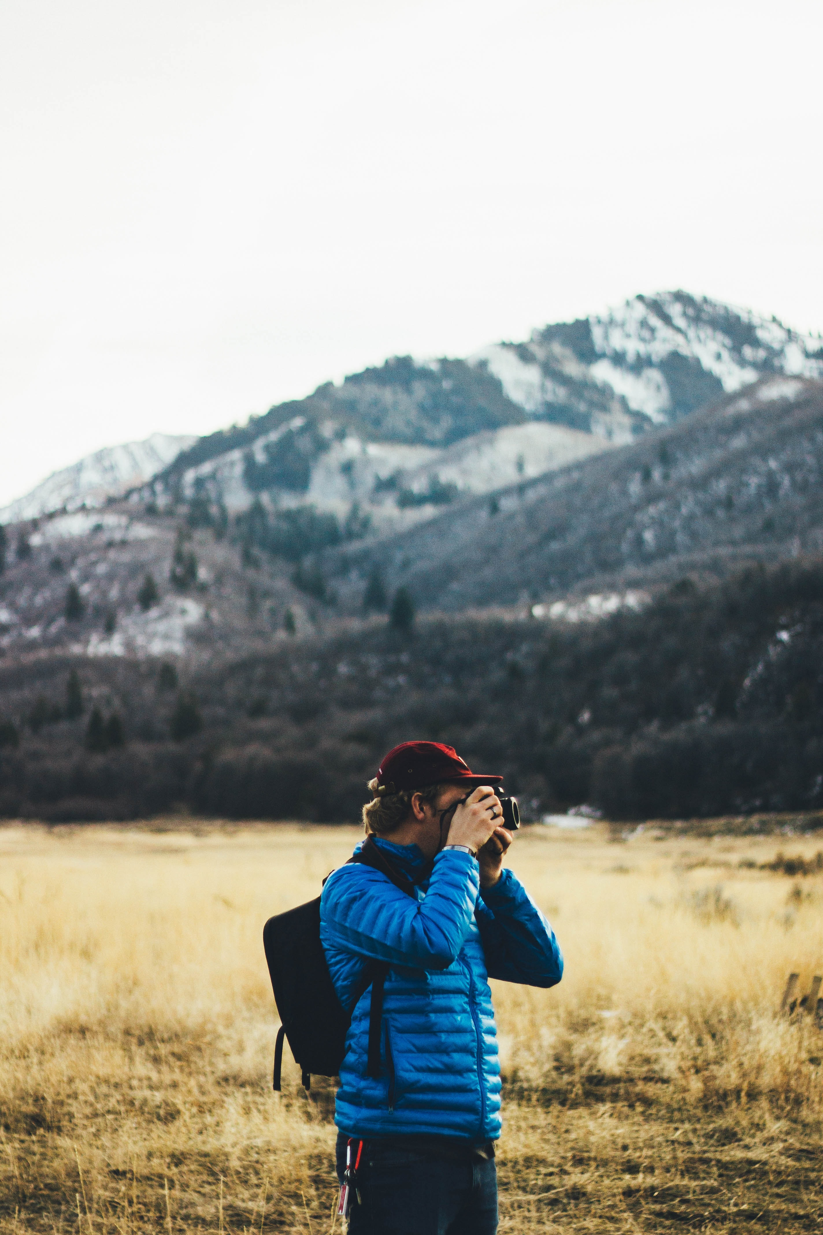 man standing near mountain taking photo