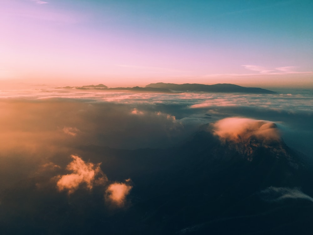 bird's eye view photo of clouds and mountains during daytime