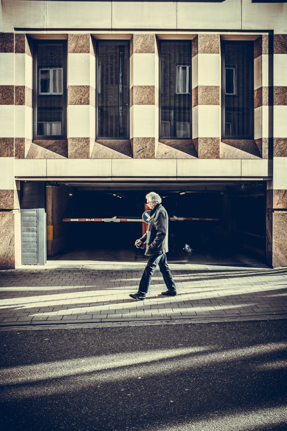 man walking on pavement in front of concrete structure