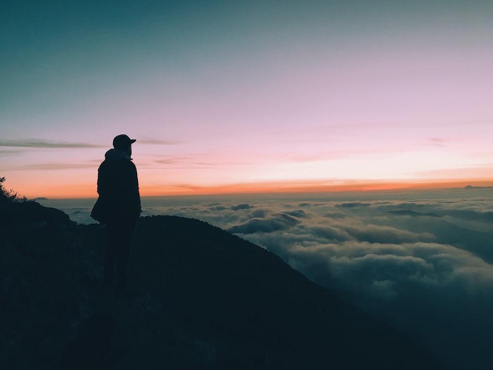 silhouette of man on hill facing horizon with orange sky