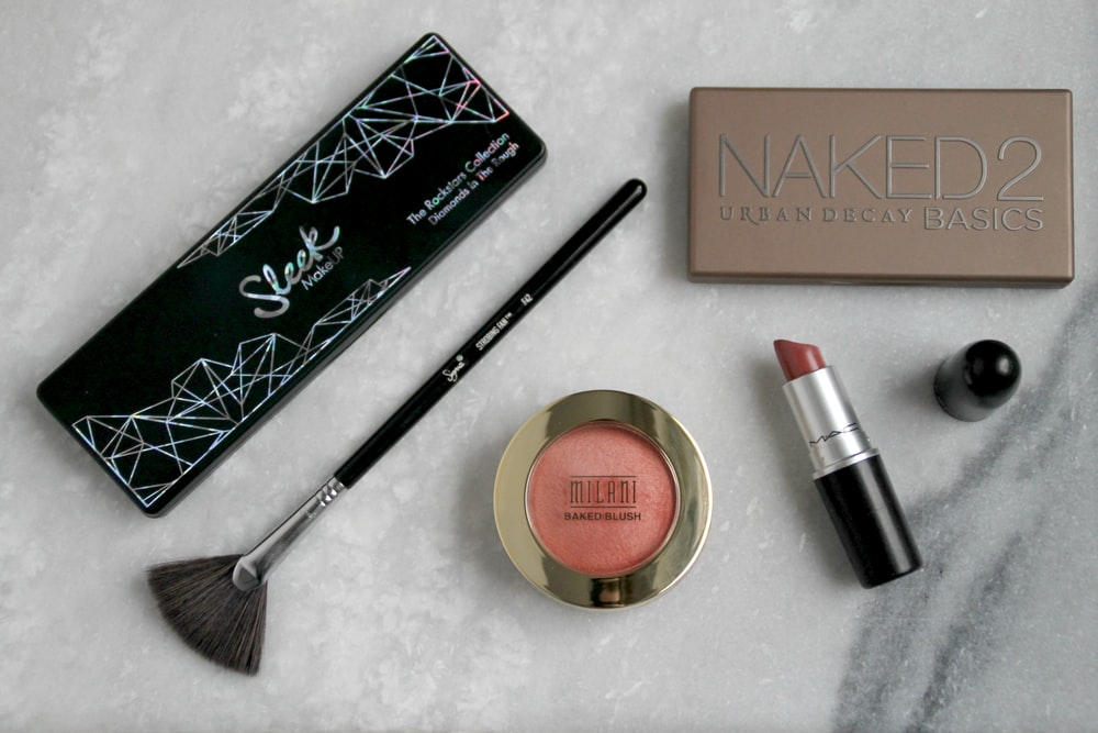 black makeup brush, lipstick, and blush on powder