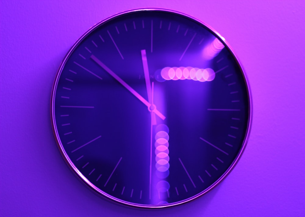 round silver-colored analog wall clock reading at 11:52