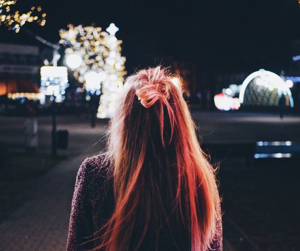 woman facing tree with lights during night time