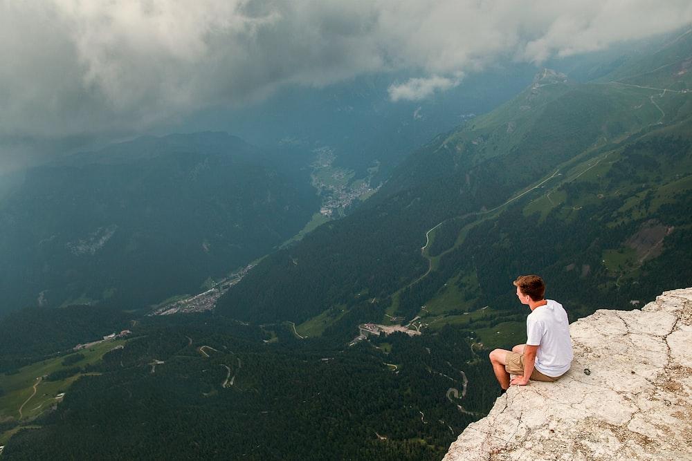 man sitting on cliff during daytime