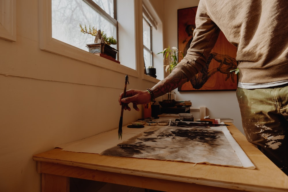 man painting on white canvas