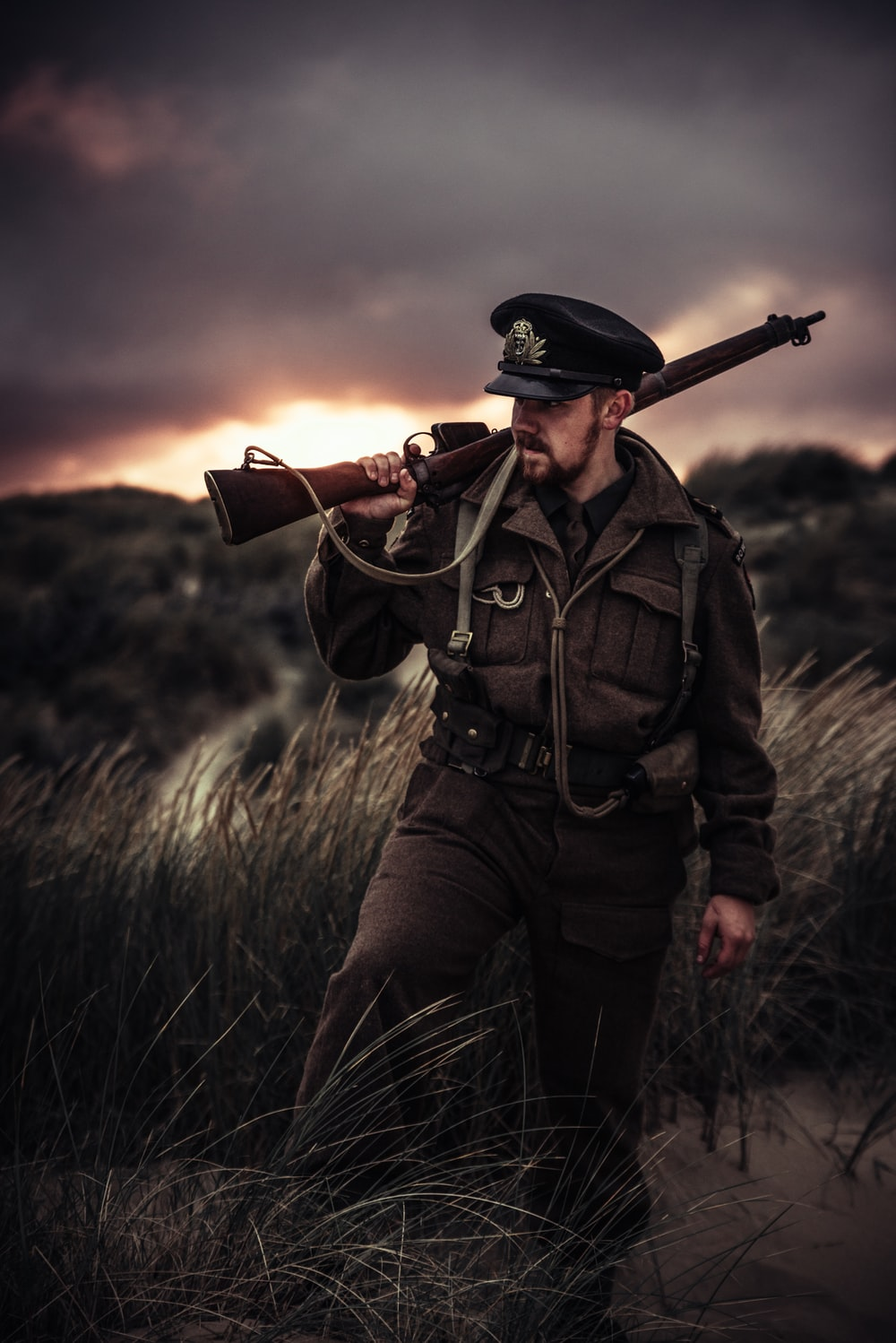 man carrying rifle outdoors