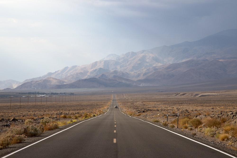 asphalt road going to mountain between grass field