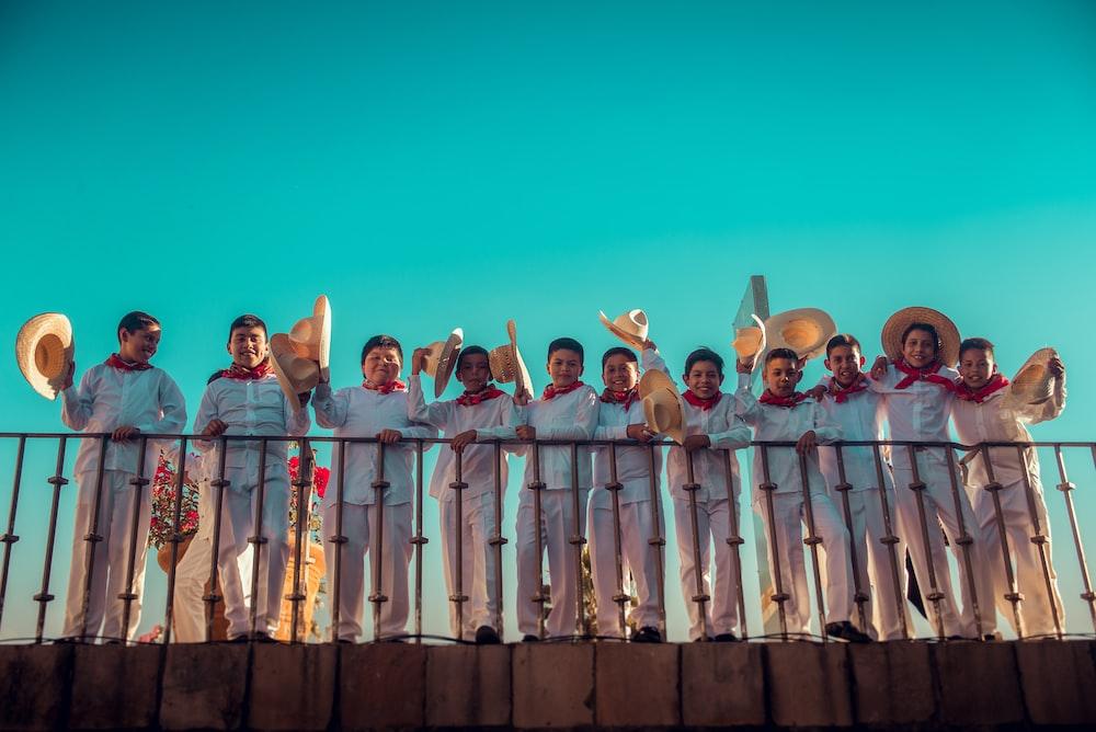 men standing on railings holding hats
