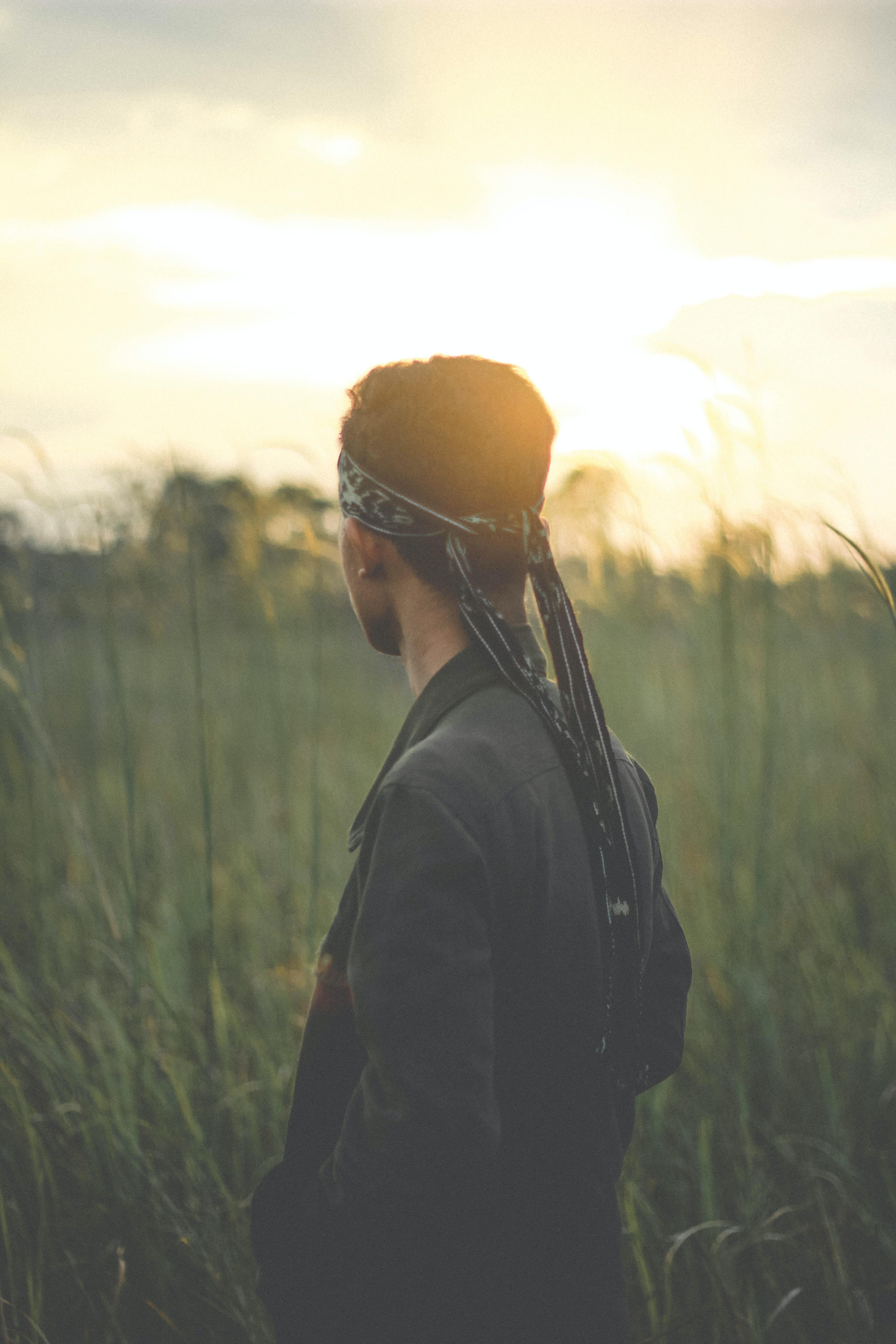 photography of man with bandana looking at grass