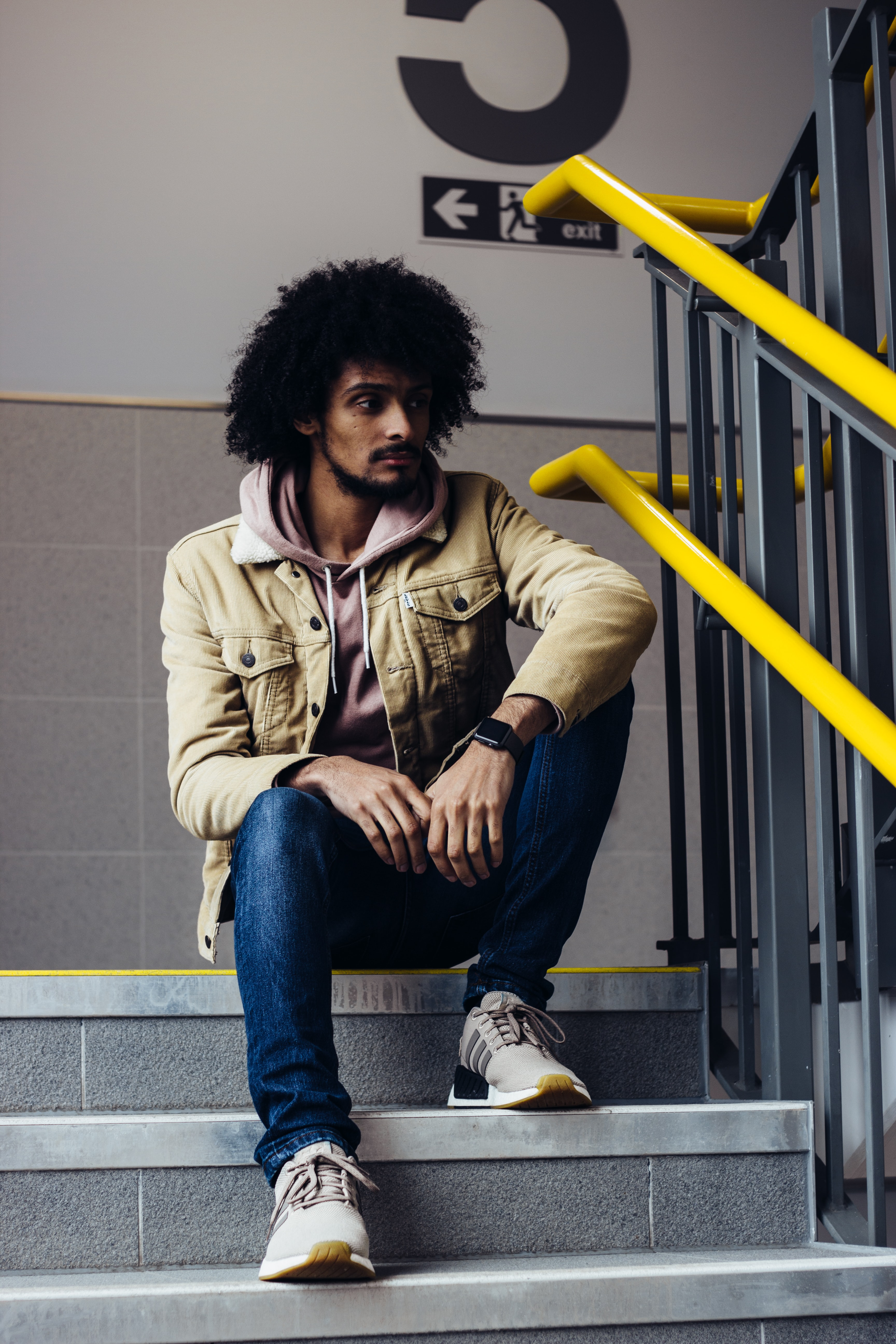 man in zip-up jacket sitting on staircase