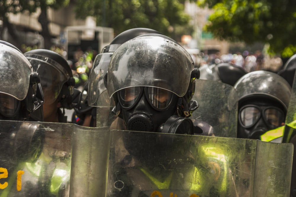 shallow focus photography of man wearing helmet and gas mask