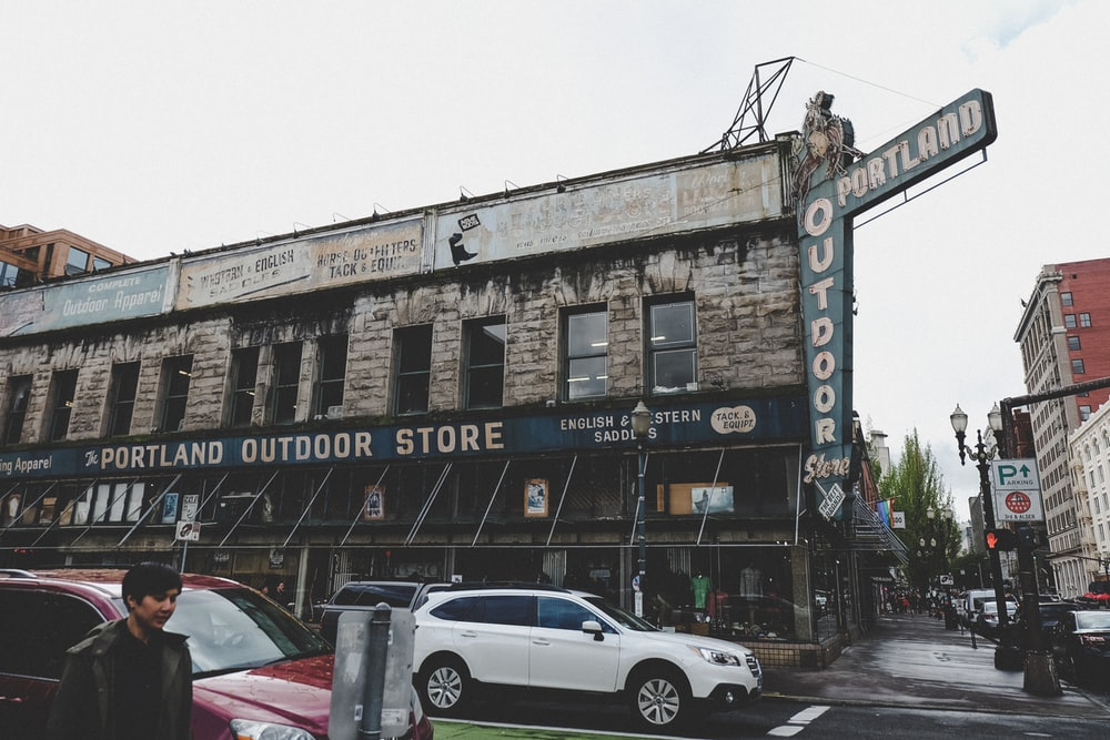man walking on street beside vehicles and Portland Outdoor Store during daytime