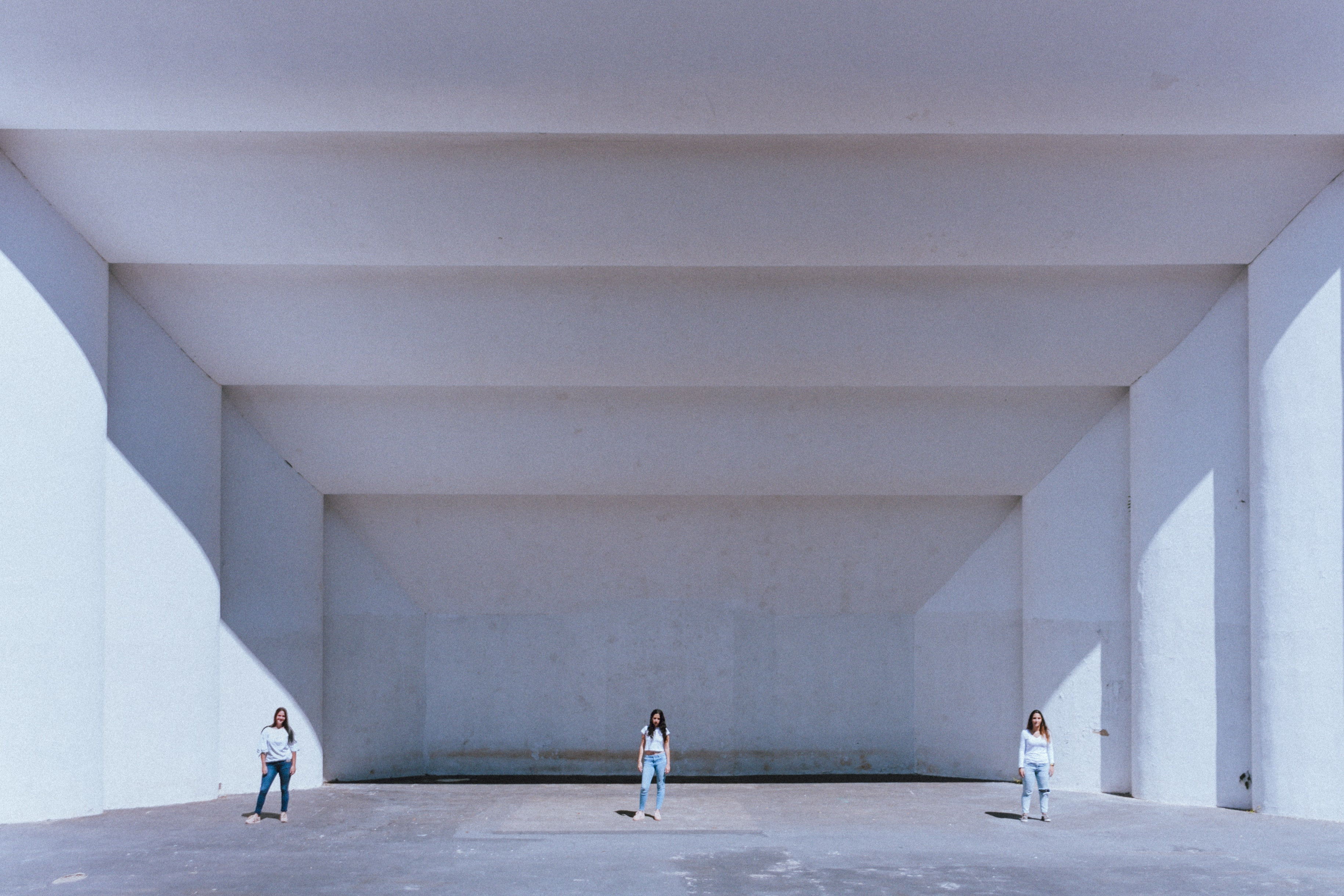 three women standing near white concrete building during daytime