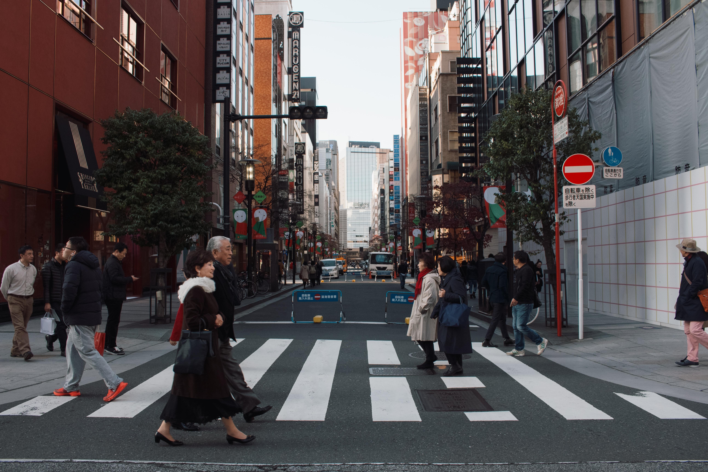 people crossing on road between buildings during daytime