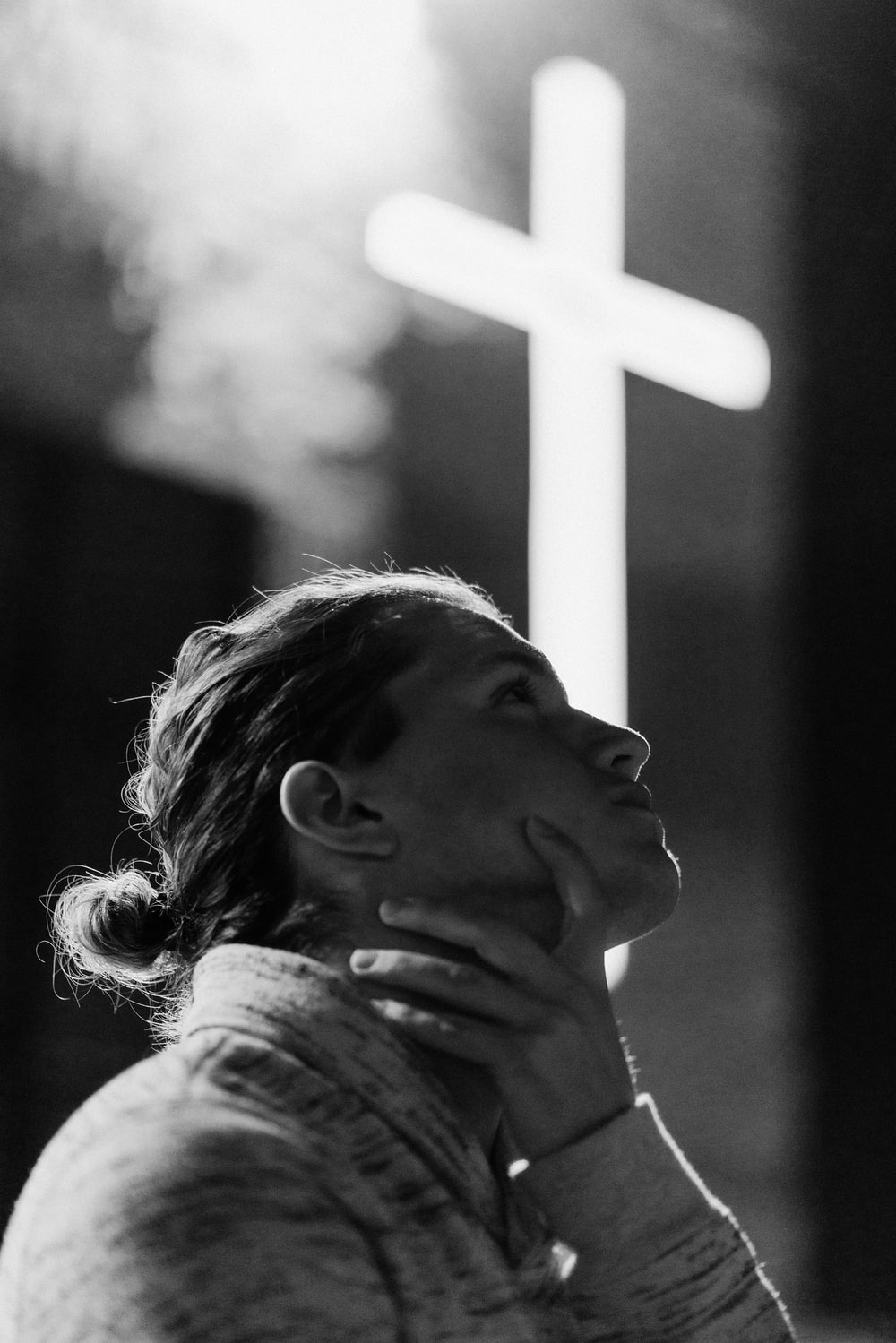 grayscale photography of woman standing near white cross signage