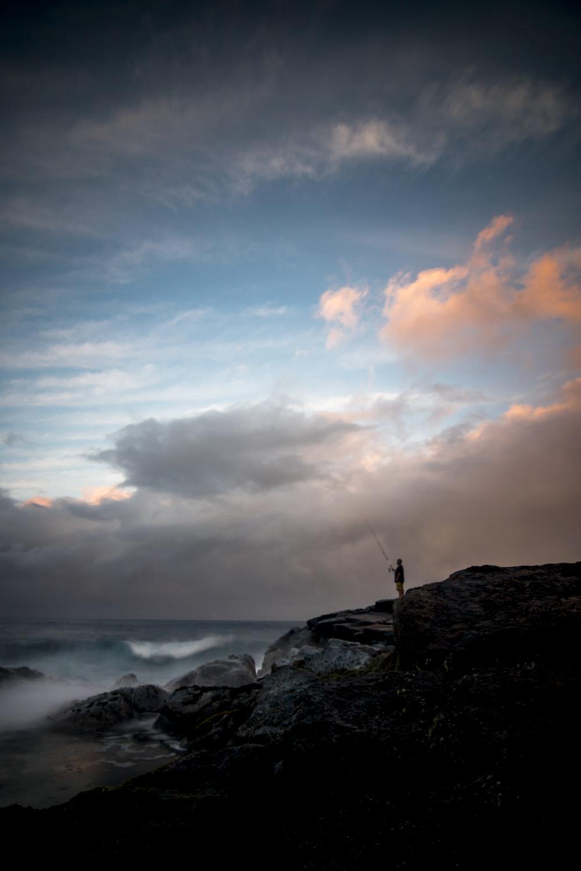 man standing on cliff fishing during daytime