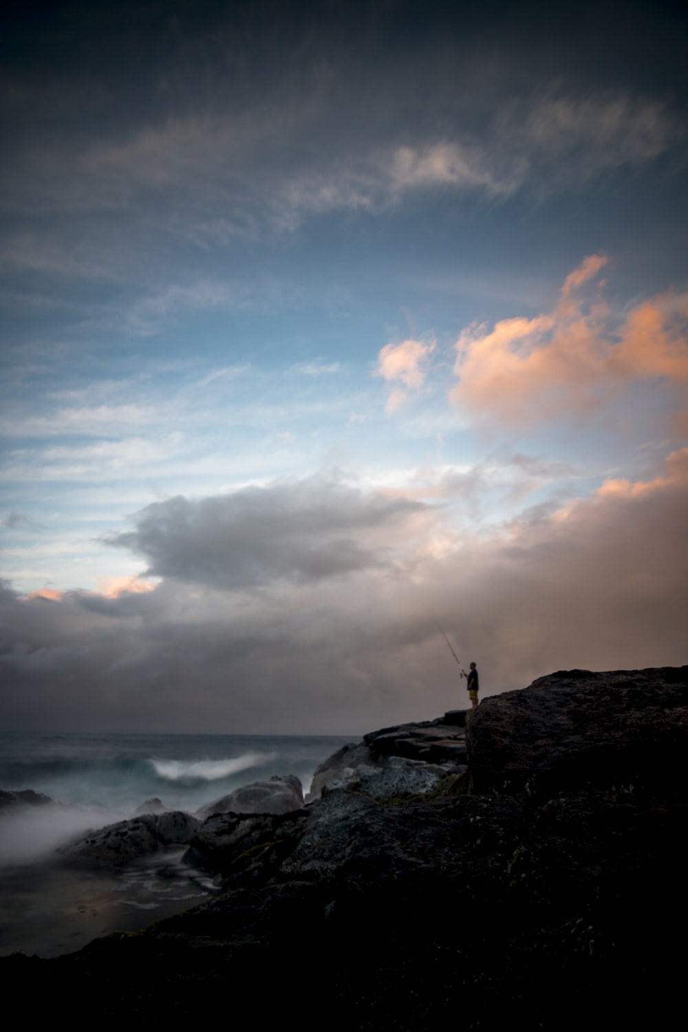 man standing on cliff fishing during daytime