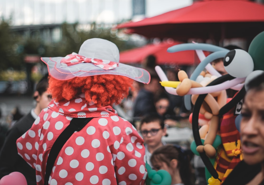 clow wearing white sun hat surrounded with people during daytime