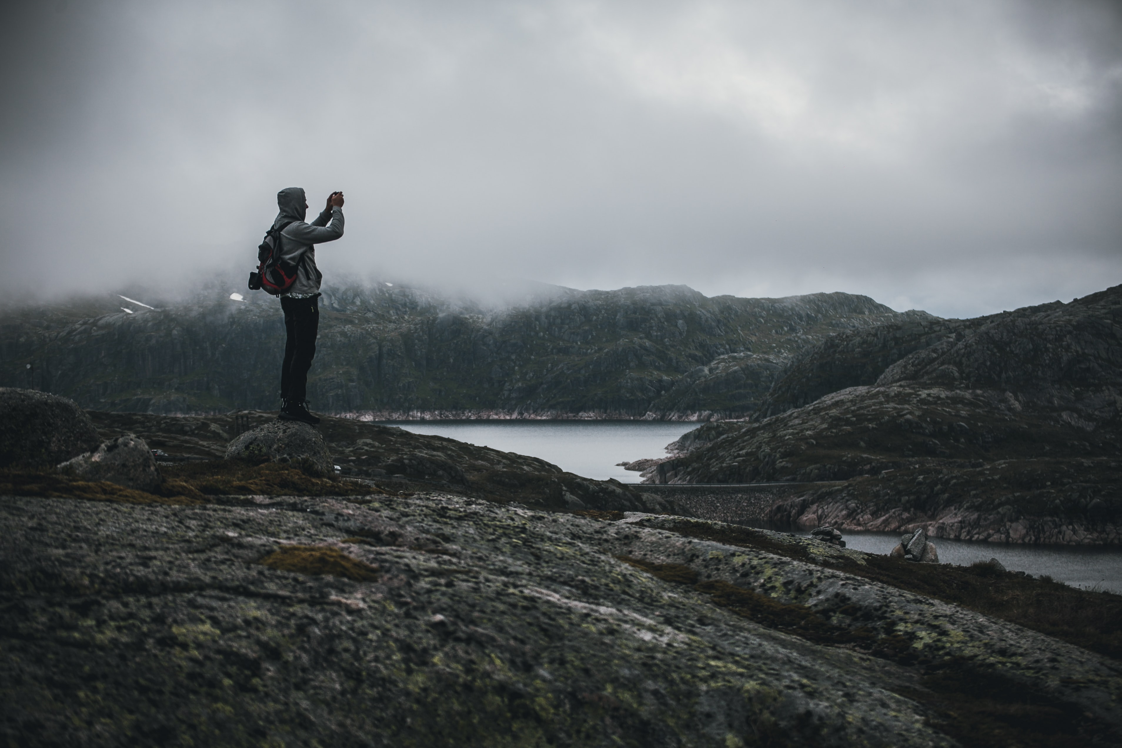 man standing on stones taking photo of mountain near body of water during foggy day