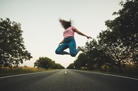 woman in pink top and blue pants jumps on road