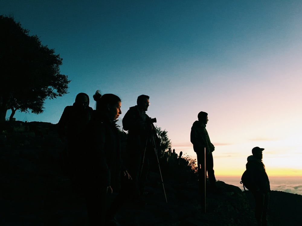 silhouette of group of people standing on hill