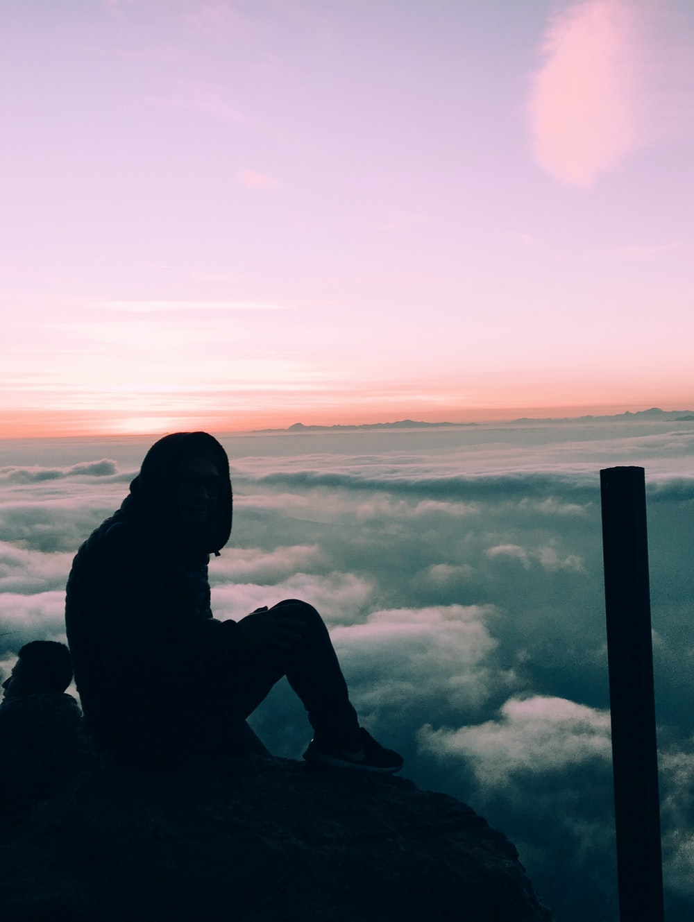 silhouette of person sitting on cliff seeing sea of clouds
