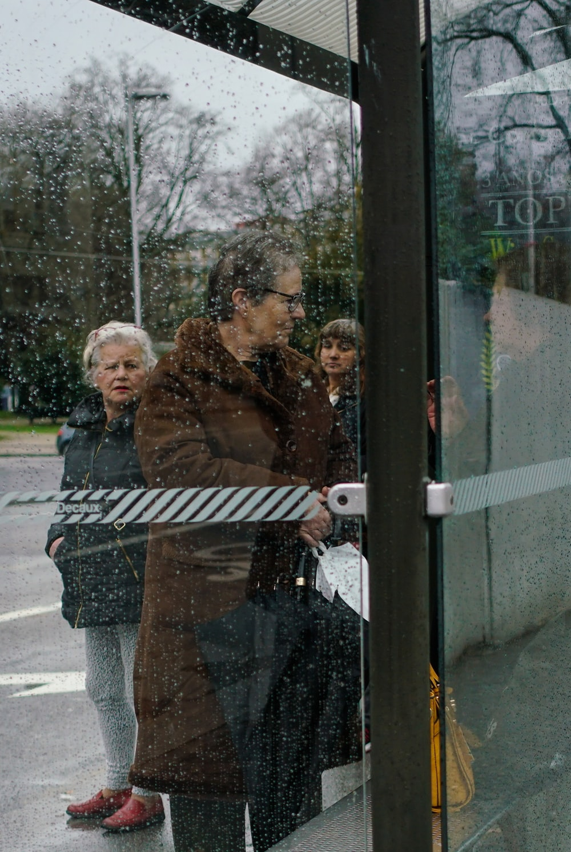 person holding umbrella near glass door