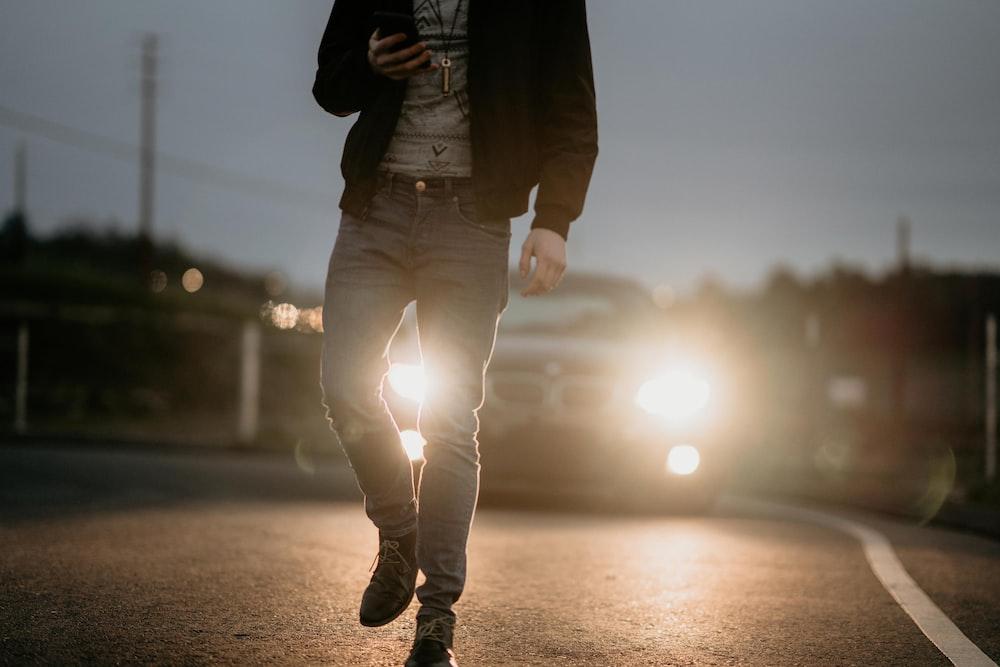 man in black jacket walking on street
