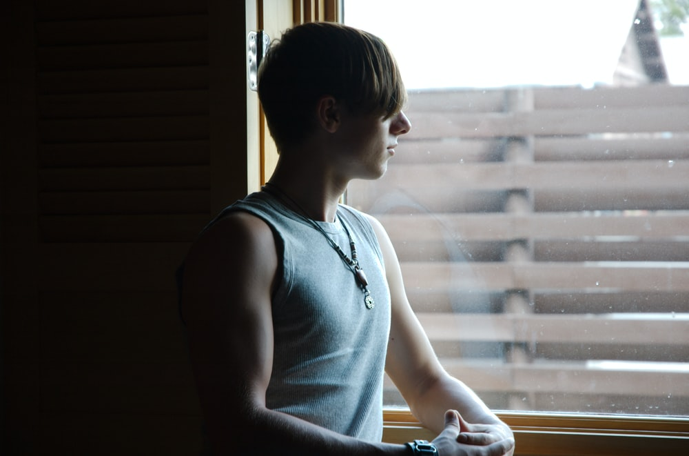 man in blue tank top looking at window
