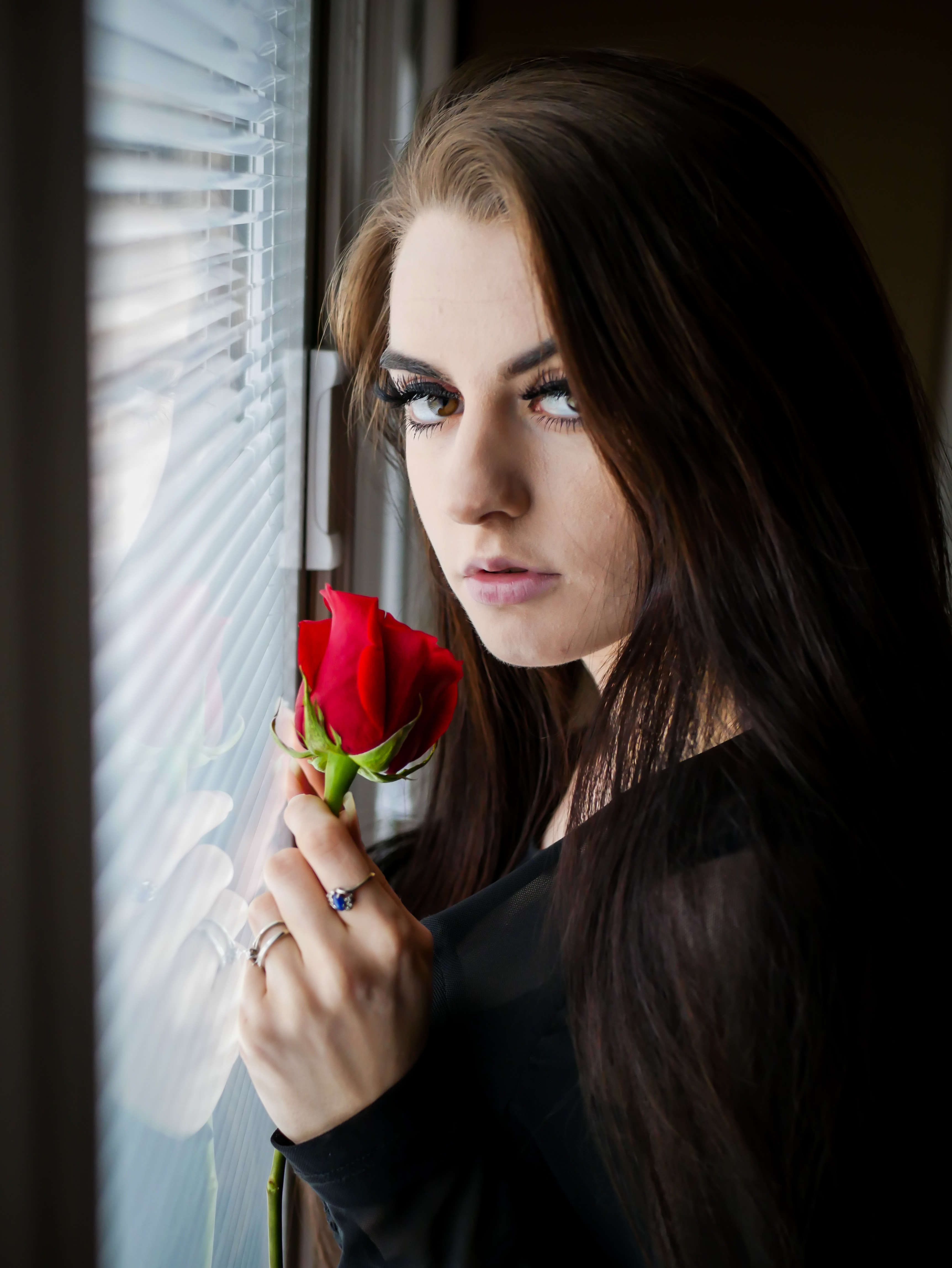 woman in black long-sleeved top holding red rose
