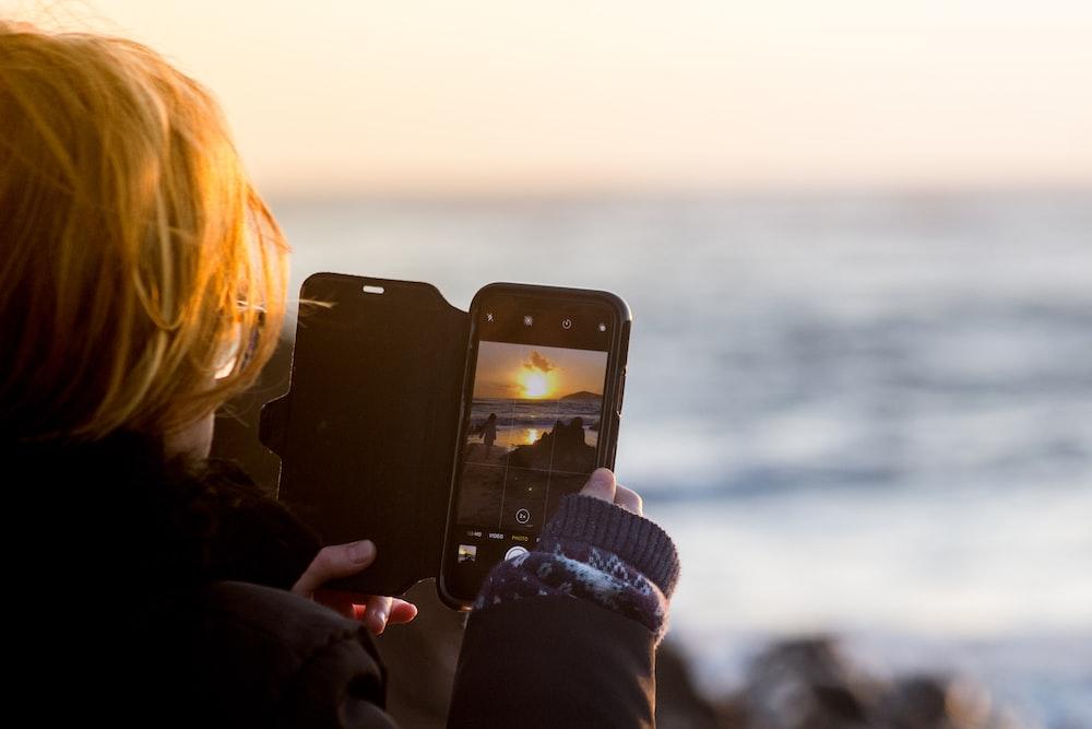 woman capturing sunset using smartphone