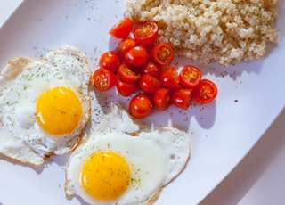 two sunny side eggs with sliced tomatoes on ceramic plate