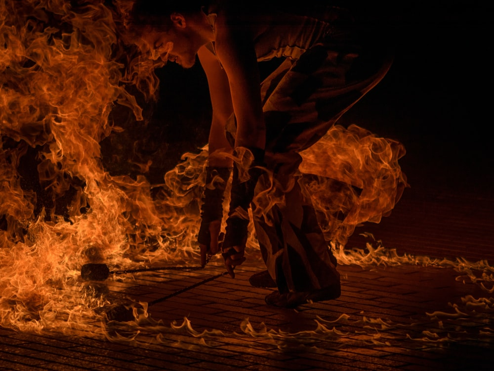 male fire dancer holding two torches surrounded by fire