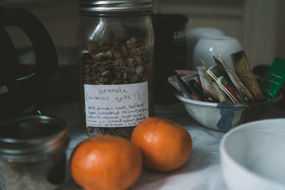 two orange fruits beside Granola labeled clear glass jar