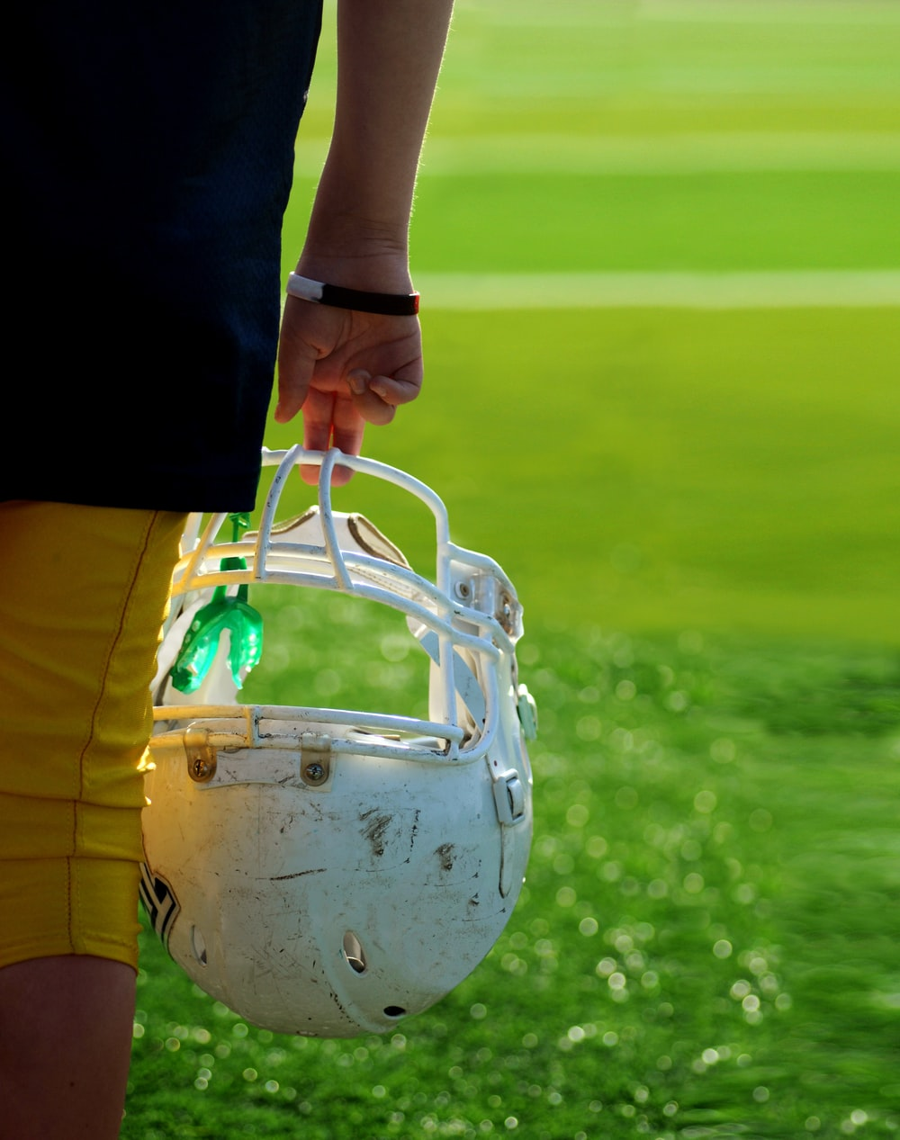 shallow focus photography of football player holding helmet