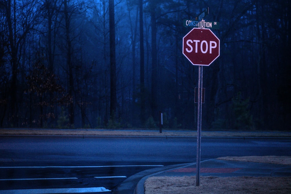 stop road sign on sidewalk near forest