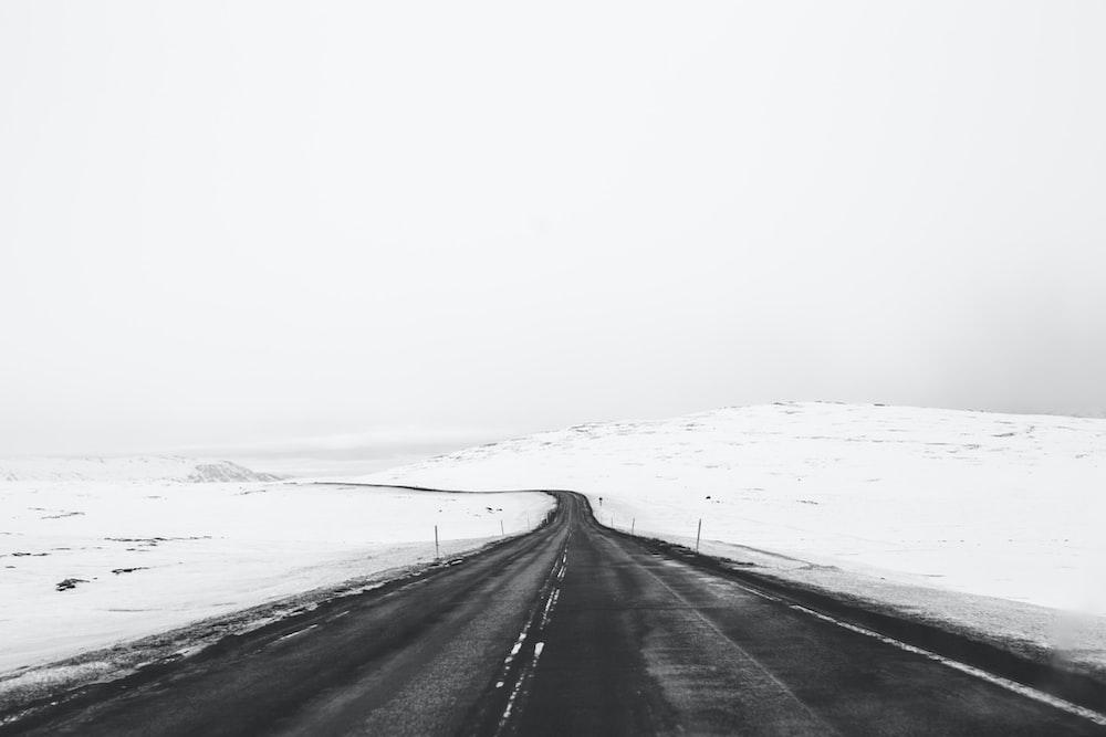 photo of asphalt road towards snow field