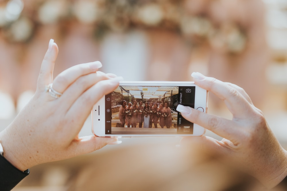 person holding iPhone capturing group of women