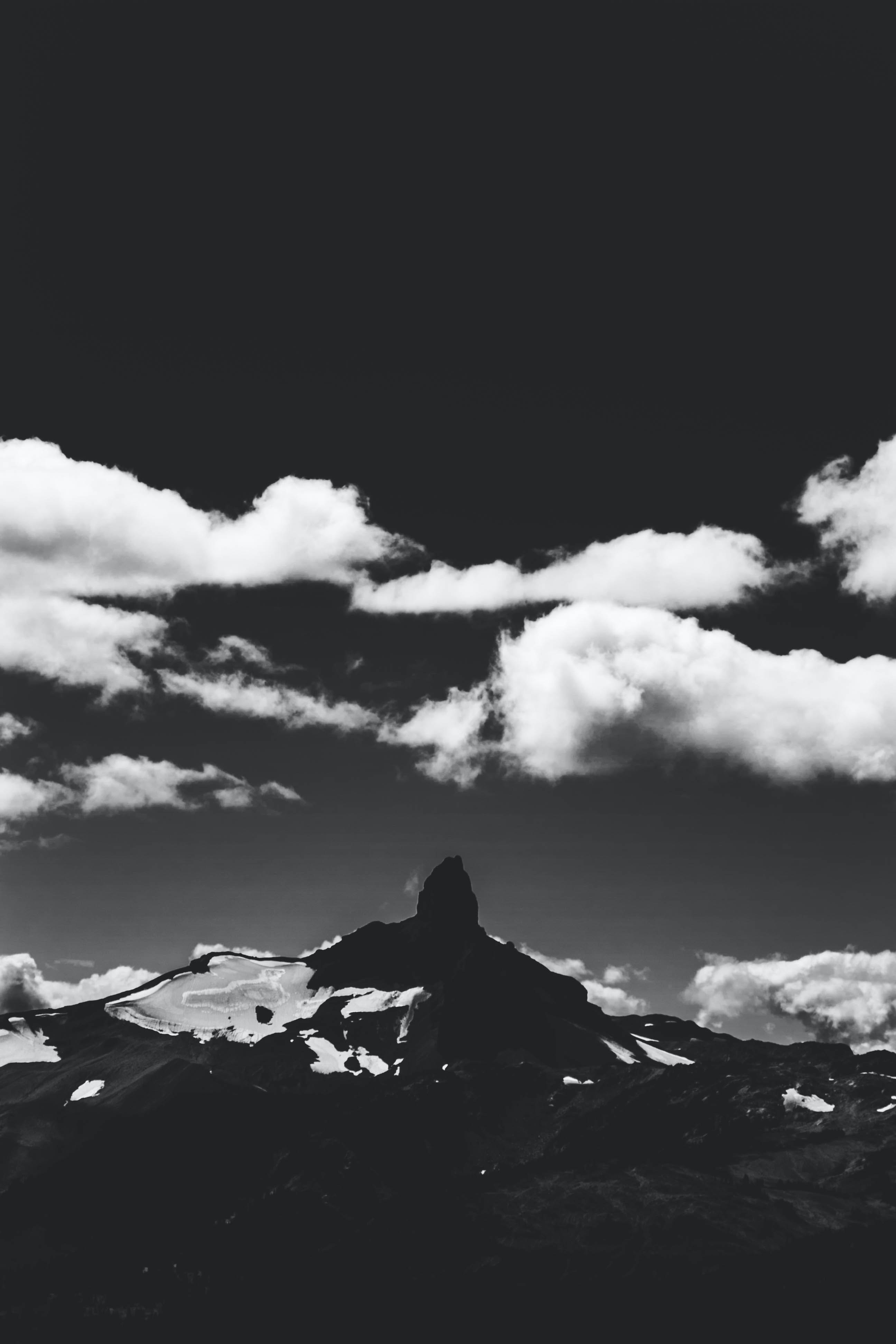 grayscale photography of mountain and clouds