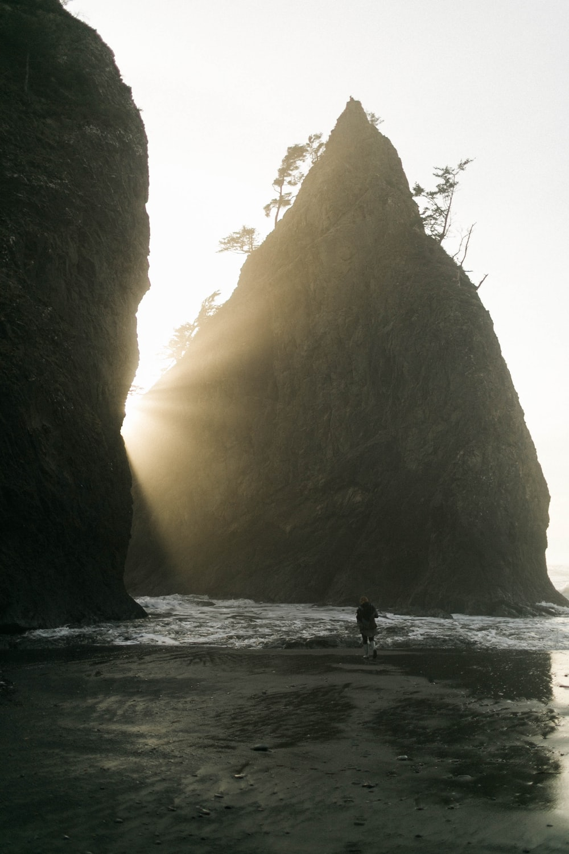 person walking on seashore near boulder