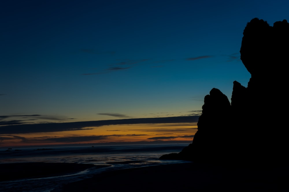 landscape photography of rock formation near body of water during nightime