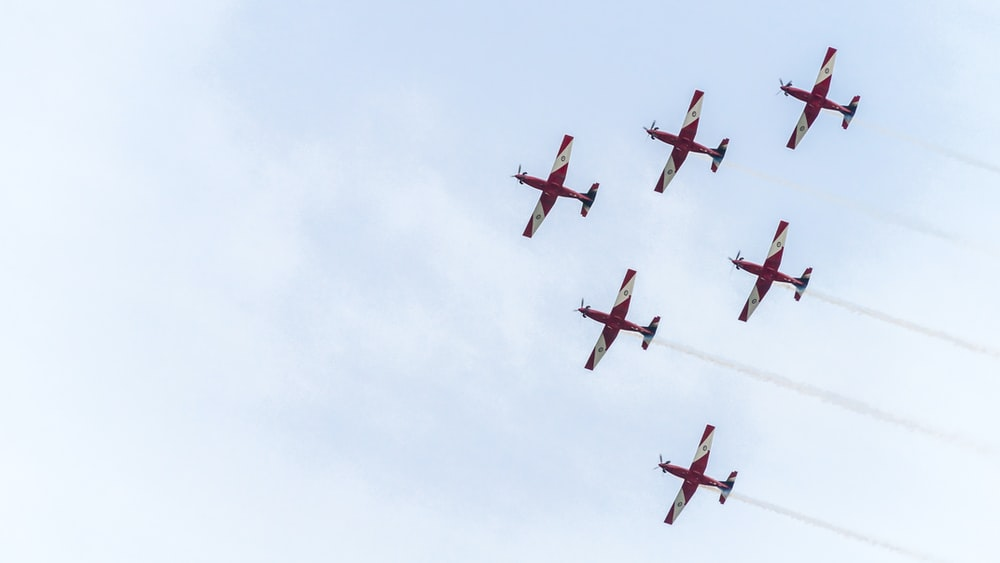 six red planes under white sky during daytime