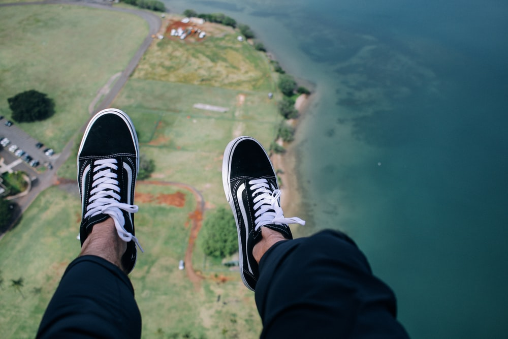 person wearing blue-and-white VANS low-top sneakers with aerial view of body of water