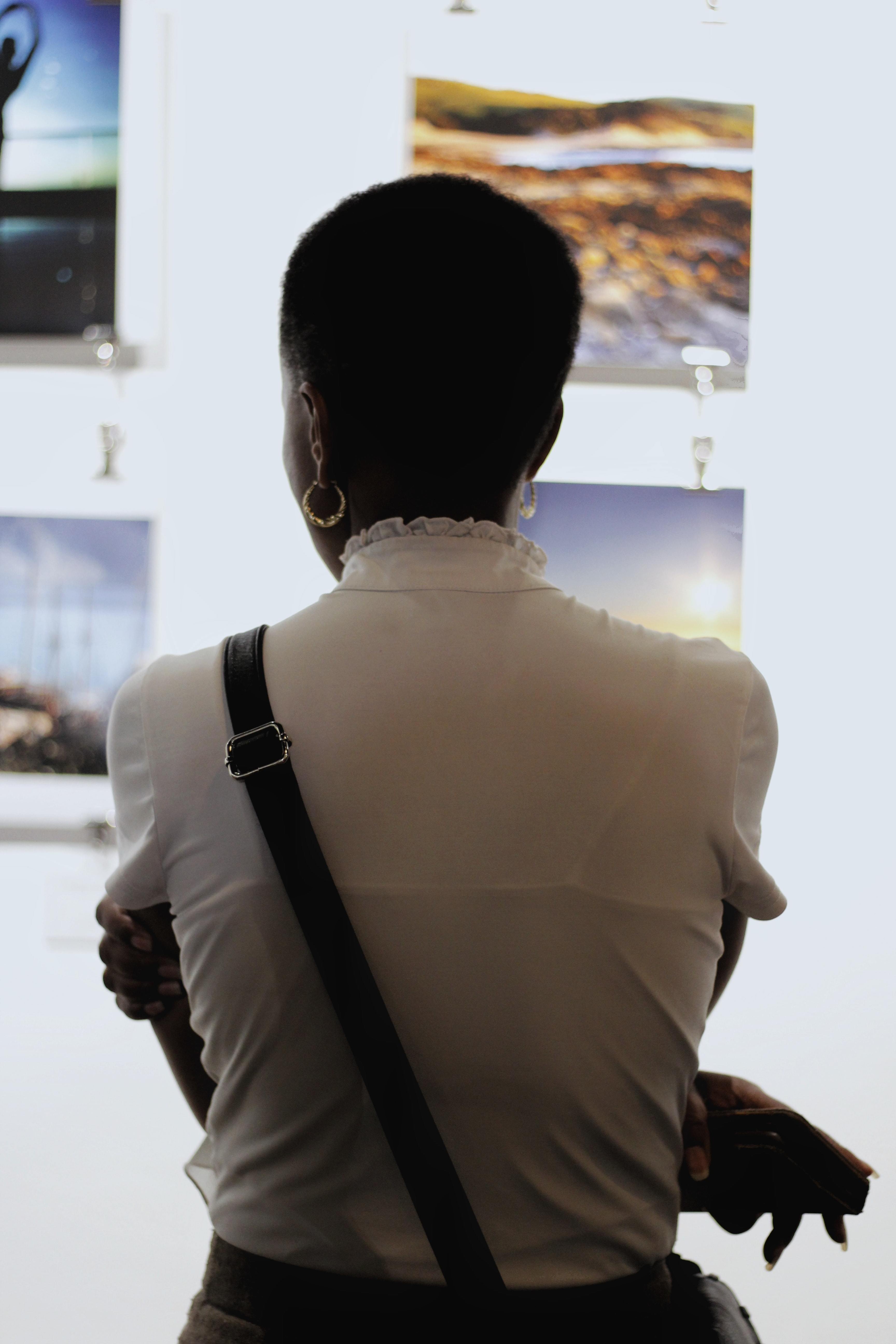shallow focus photography of woman crossing her both arms while looking images in wall