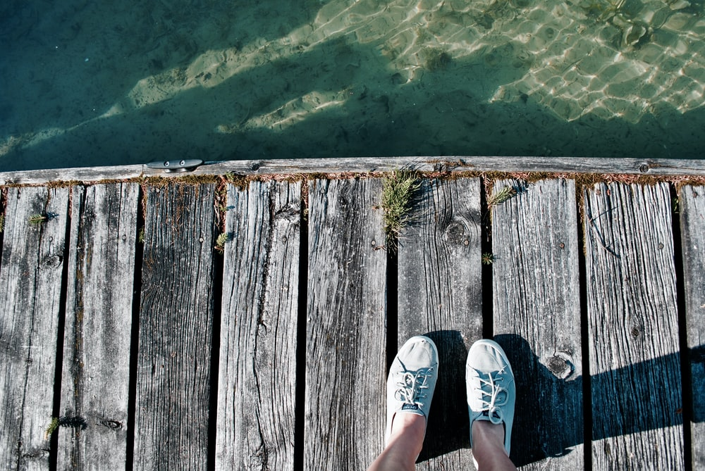 person standing on wooden dock over body of water