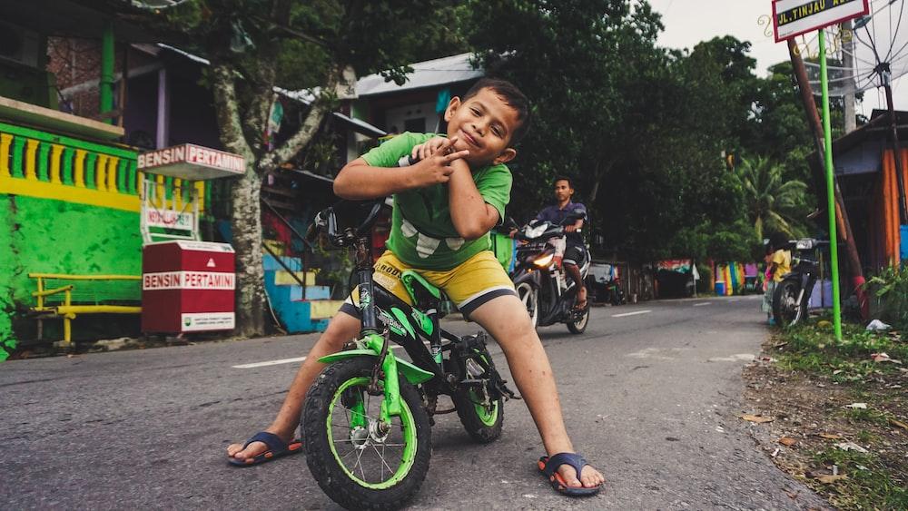 boy riding black and green bike near man riding motorcycle at daytime