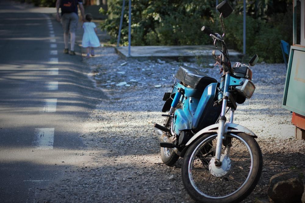 blue moped motorcycle near road