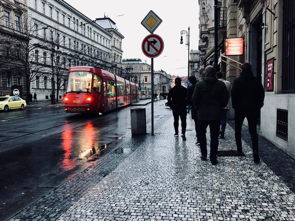 people walking beside street light near lighted signage