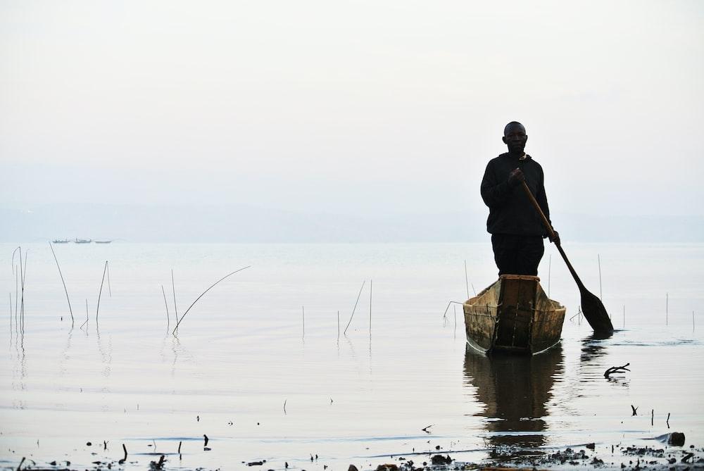man riding brown canoe